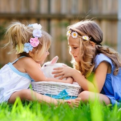 Zdjęcie przedstawia dwie dziewczynki w ogródku, które siedzą przy koszyczku wiklinowym w którym znajduje się królik.