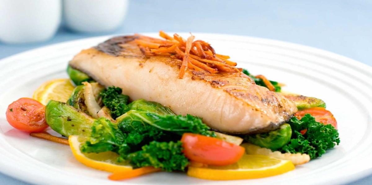 Zdjęcie przedstawia danie rybne - filet rybny z dodatkami warzyw.