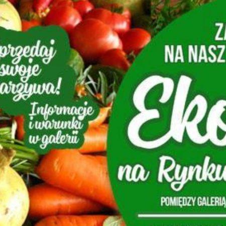 Plakat graficzny zapraszający w sobotę do Jezioran na cotygodniowy Eko Targ na Rynku w Jezioranach 2021. Tłem zdjęcia są ekologiczne warzywa lokalnych producentów. Na plakacie są napisy zapraszające do uczestnictwa w imprezie.