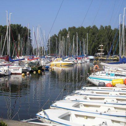 Ekologiczna przystań żeglarska Korektywa w Piaskach. Na zdjęciu zacumowane jachty w porcie.
