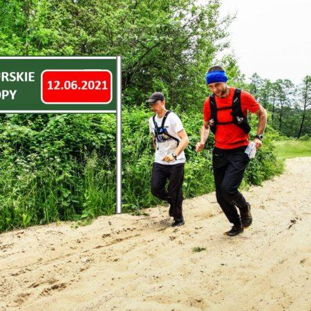 Zdjęcie zapraszające do Stawigudy na 8. edycję Mazurskie Tropy - Stawiguda 2021. Na zdjęciu widzimy dwóch zawodników zawodów podczas biegu na leśnej drodze.
