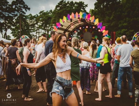 Zdjęcie z Festiwalu Wibracje, który promuje dbanie o siebie, ekologię, zrównoważony rozwój, życie w harmonii i zdrowiu ze sobą i otaczającym światem. Na zdjęciu kobieta tańcząca podczas koncertu.
