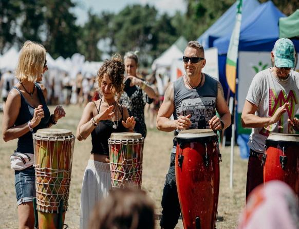 Zdjęcie przedstawiające koncert na bębnach z Festiwalu Wibracje, który promuje dbanie o siebie, ekologię, zrównoważony rozwój, życie w harmonii i zdrowiu ze sobą i otaczającym światem. Na zdjęciu cztery osoby grające na bębnach.
