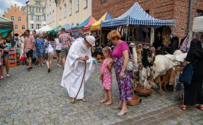 Zdjęcie wykonane podczas odbywającego się w latach poprzednich Jarmarku Jakubowego na Starym Mieście w Olsztynie. Na zdjęciu widzimy spacerujących turystów i mieszkańców Olsztyna pomiędzy straganami.