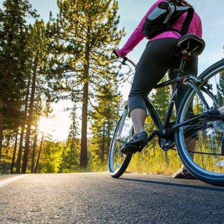 Na zdjęciu widzimy turystkę na rowerze stojącą na drodze przed lasem, podczas wyprawy rowerowej.