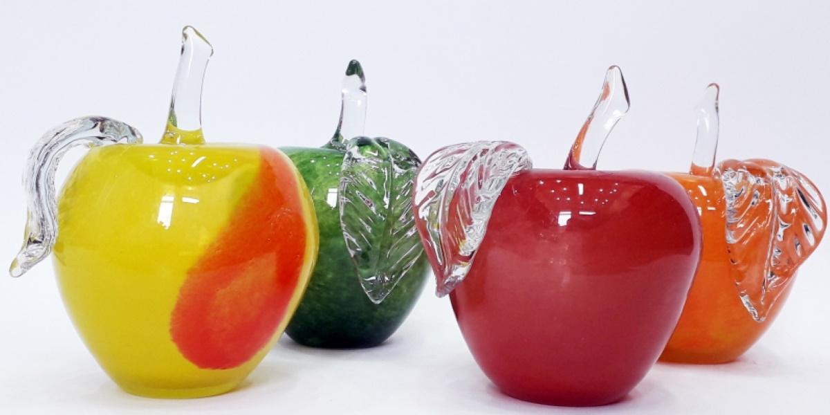 Wyroby szklane z Huty Szkła w Olsztynku. Na zdjęciu cztery szklane jabłka o różnych kolorach.