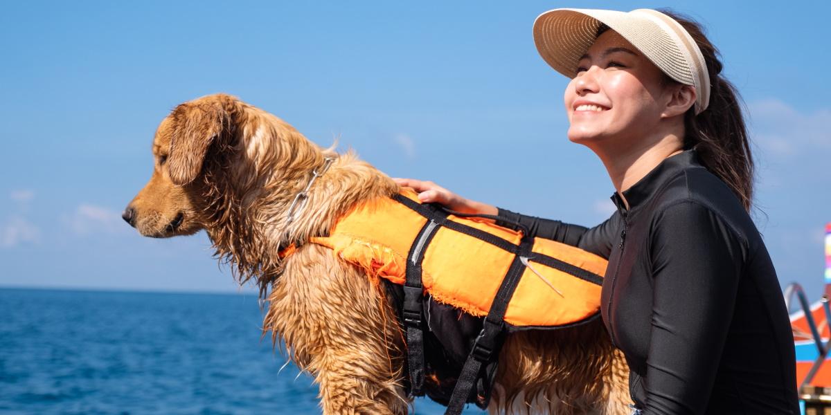 Zdjęcie psa i kobiety siedzących nad wodą.