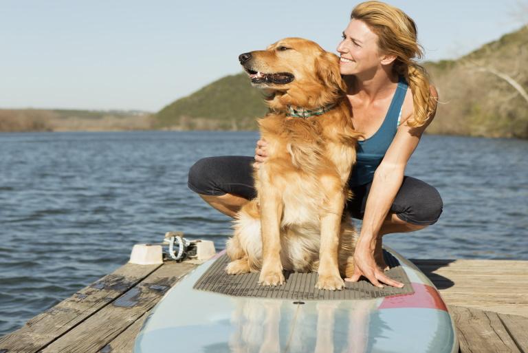Zdjęcie przedstawia kobietę i psa siedzących na desce windsurfingowej na pomoście nad jeziorem.